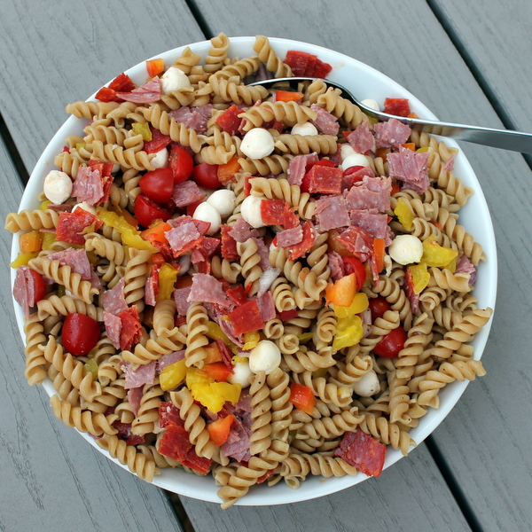 Salty, spicy Italian antipasto fixings are paired with fresh veggies and whole wheat pasta to create an Italian Antipasto Pasta Salad, a delicious side that's also hearty enough to enjoy for lunch.