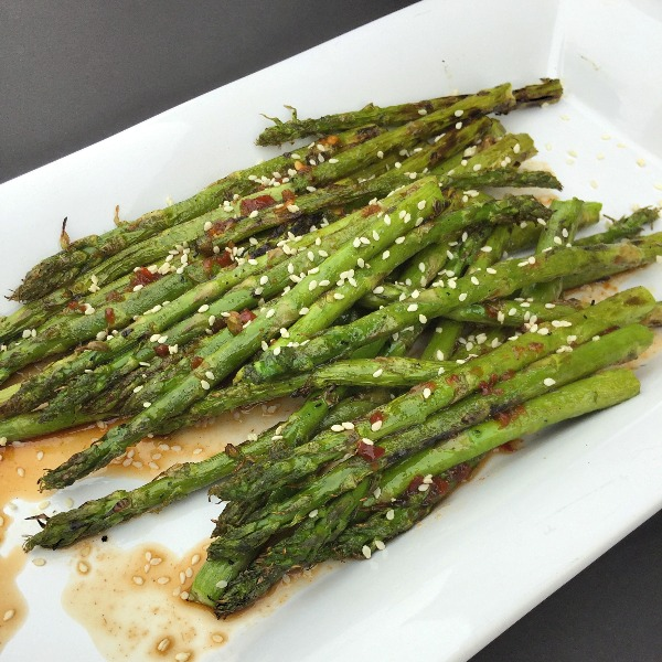 Asparagus brushed with sesame oil is grilled and then tossed with a sweet-spicy sauce and topped with toasted sesame seeds for a delicious summer side dish.