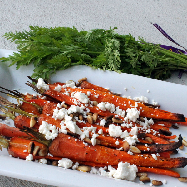 Carrots are roasted until browned but still crispy and then topped with toasted pine nuts and salty feta for a light, bright, flavorful side dish.