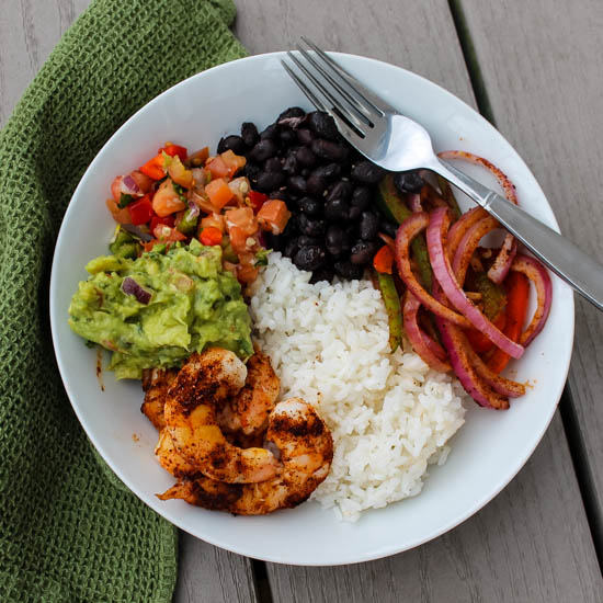 This big, bold Taco Shrimp Bowl - easily customizable to your tastes - can be on your table in under 30 minutes. Make it for Cinco de Mayo, Taco Tuesday, or a quick weeknight meal. The shrimp and veggies are cooked on a sheet pan before being served with rice, garlicky black beans and your favorite taco toppings.